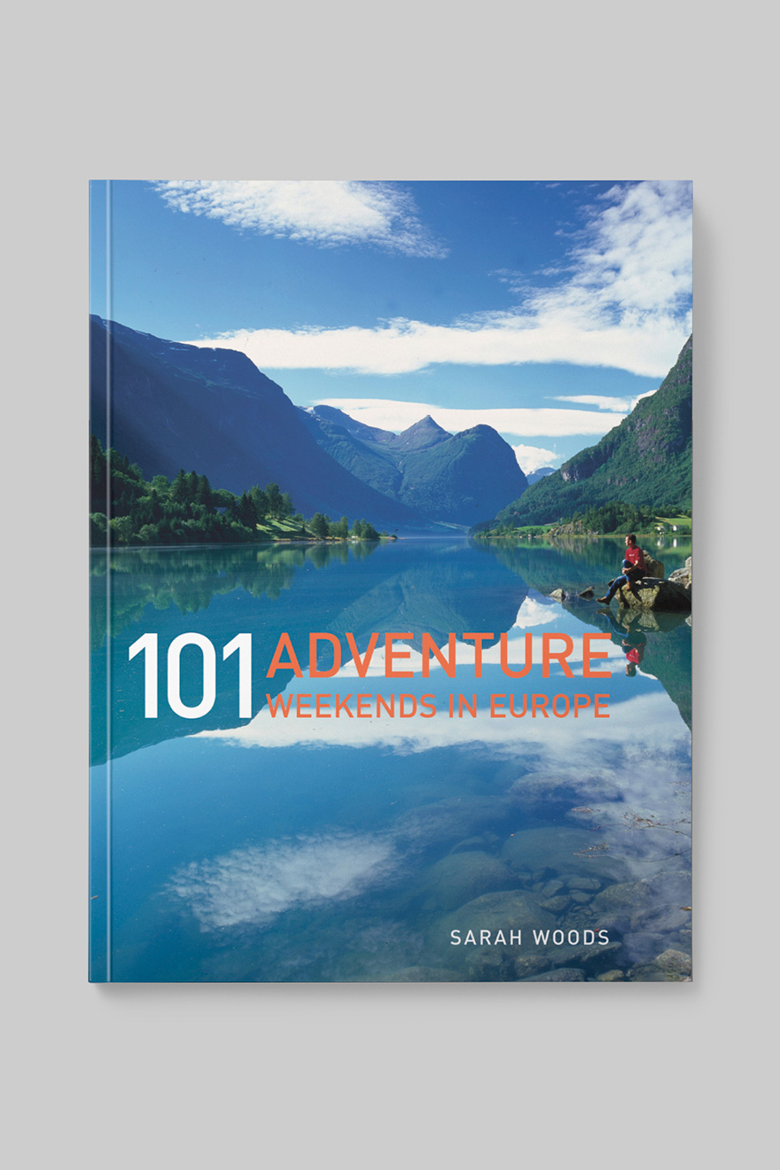 Front book cover to 101 Adventure Weekends in Europe, showing a hiker sitting next to a lake